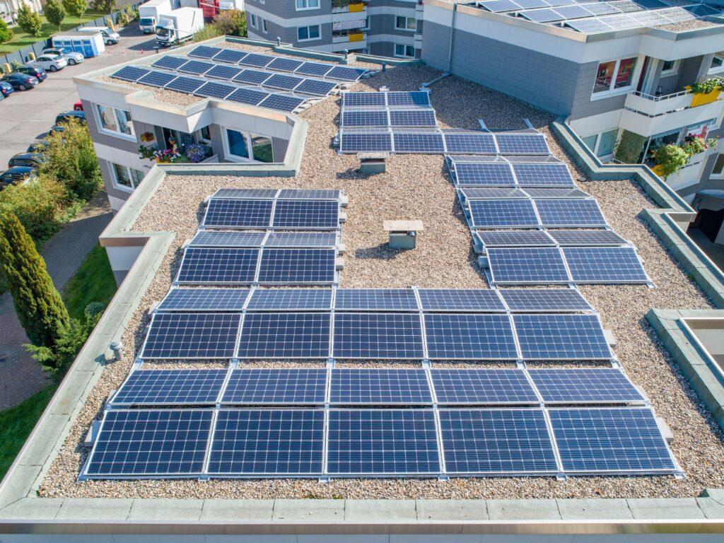 dienstleistungen-photovoltaikanlage-dachflaeche-erneuerbare-energie-dach-kies-balkon-grünpflanzen-parkplatz-solar